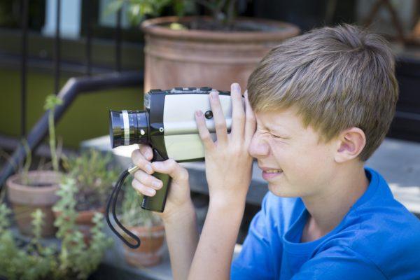 Vierzehnjaehriger Junge mit einer alten analogen Videokamera.